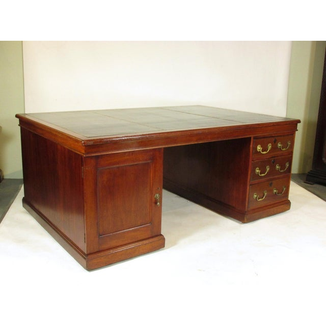 An outstanding English Edwardian mahogany grand partner's desk with a kneehole flanked by three drawers on one side and a...