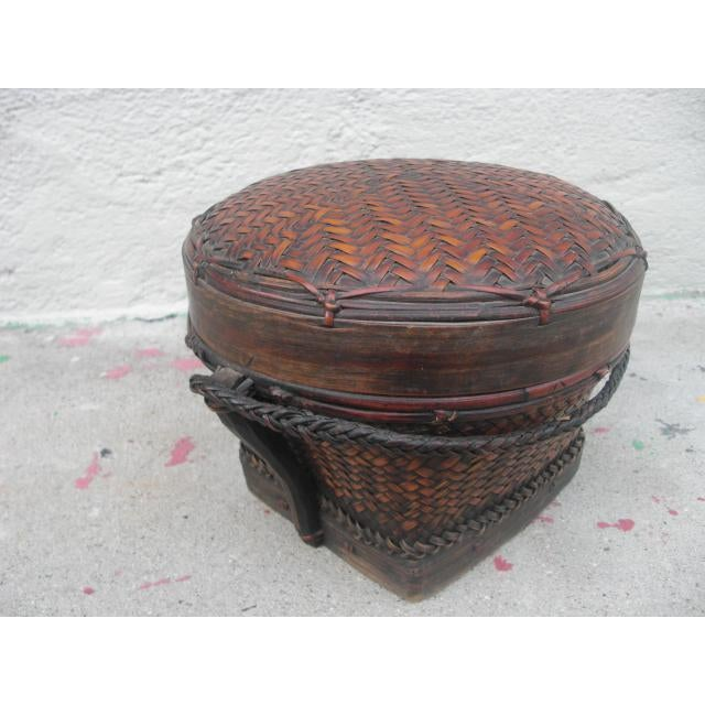 Medium-sized, antique, lidded rice basket with an attached braided rope handle and a wonderful aged patina. A stylish...