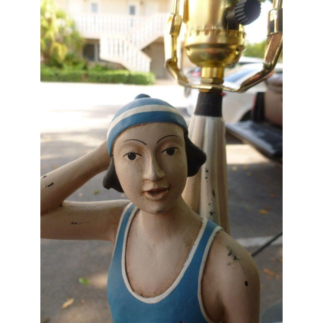 This is a vintage, whimsical wooden figure in swimming suit lamp. The piece is great for a beach house.