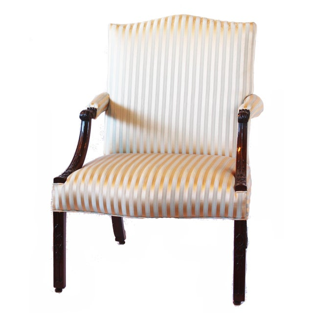 A George III mahogany library armchair in the manner of Thomas Chippendale, the rectangular padded back and seat covered...