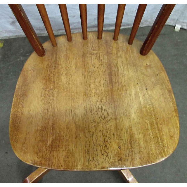 Wooden oak natural stain Windsor chair on a cross four leg base set on casters. This is a rare chair great for a desk.