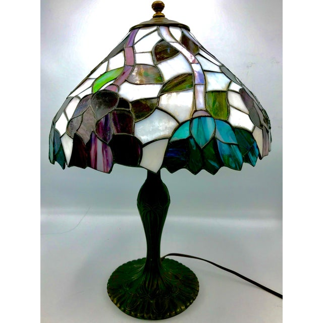 Very pretty Tiffany style stained glass Lamp with Art Nouveau cast metal base. The shade is in whites, purples, teals,...