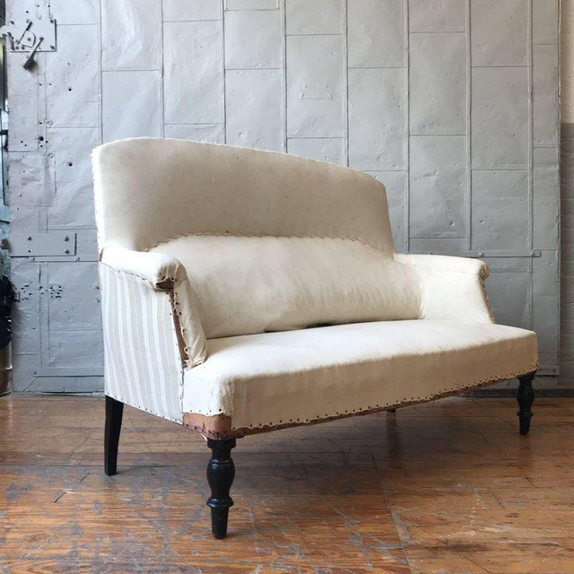 Small French NAP III high back loveseat in muslin, circa 1900. Sold as is. Upholstery services available, price on request.