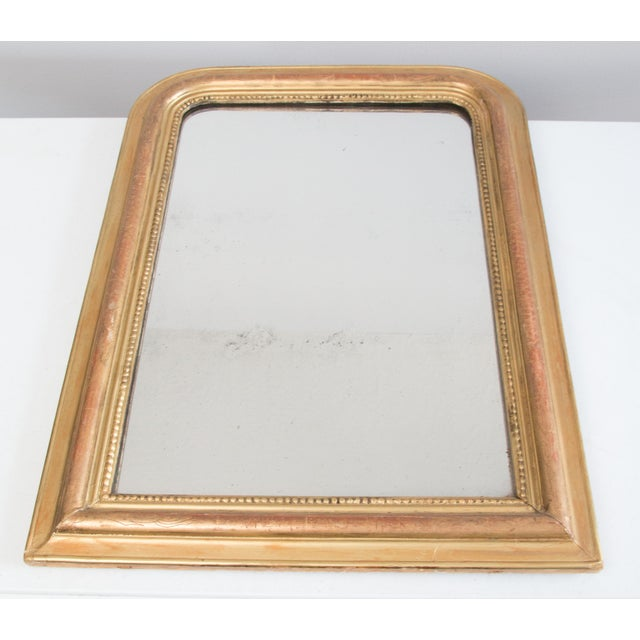 A gorgeous 19th-Century French Louis Philippe giltwood mirror. This fine mirror has lovely beaded accents, beautiful gilt...
