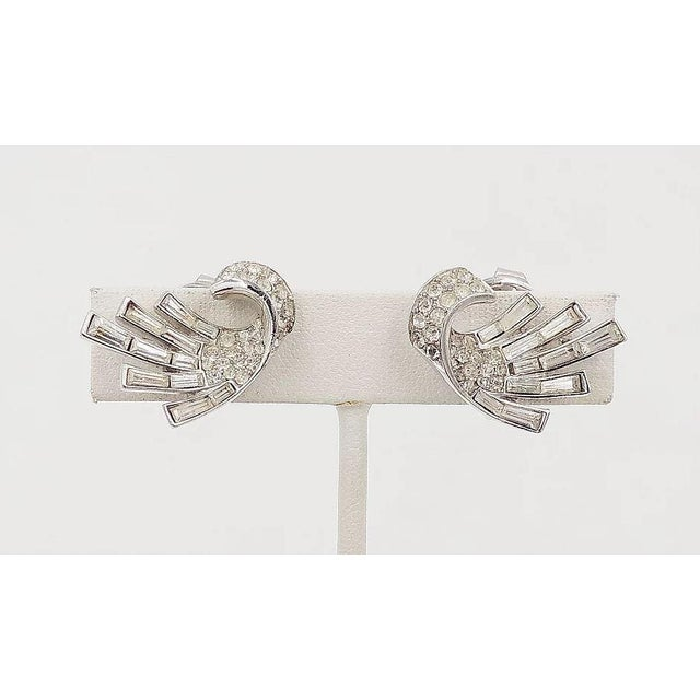"""Early 1950s rhodium plated baguette and round rhinestone clip back earrings. Marked """"Trifari."""" Measure: 15/16 inches long..."""