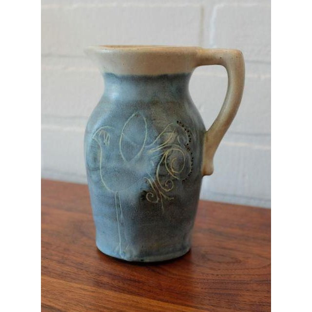 A Mid-Century Puerto Rican blue and light grey pottery pitcher, with red clay and a blue/white glaze. Decorative...