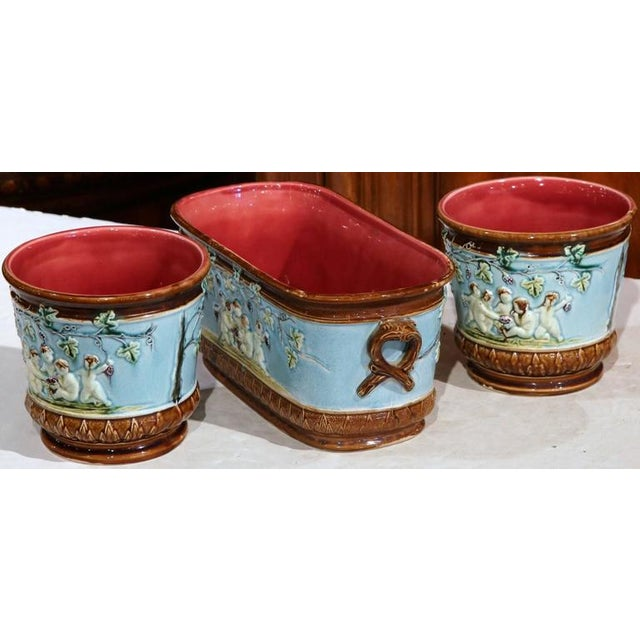 Fine antique set of three majolica planters from France, circa 1880, depicting the reign of Bacchus thru young cherubs or...