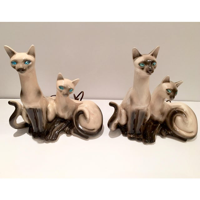 A rare & fabulous pair of 1950's California ceramic Siamese twin cat lamps. Dramatic touches to one's Hollywood Regency...