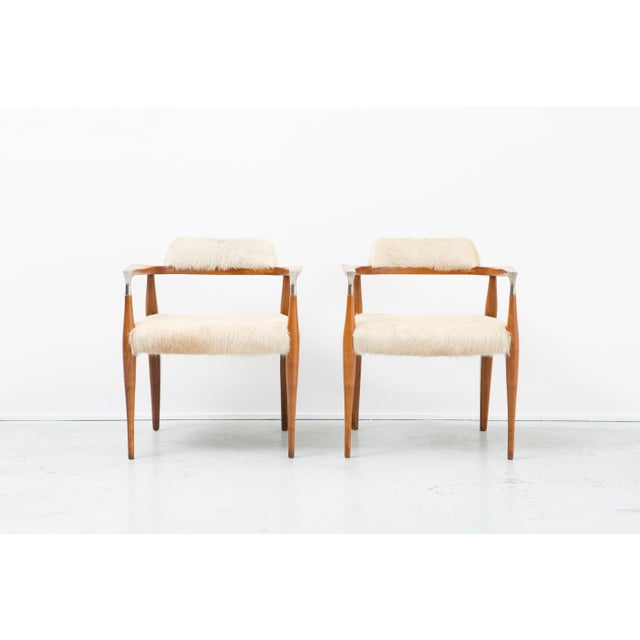 A set of two accent chairs. The designer is unknown. This piece was created circa 1950s. It has been reupholstered in...