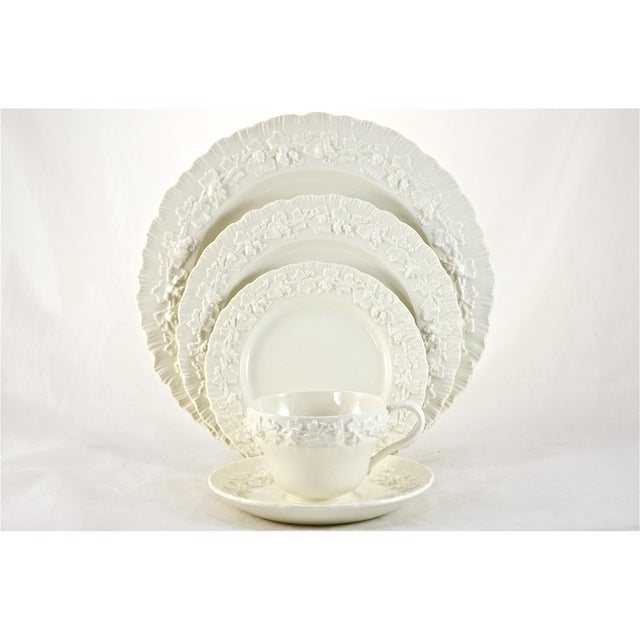 "Cream Wedgwood service for eight featuring a grape and leaf pattern with a shell edge. Marked ""Wedgwood & Barlaston of..."