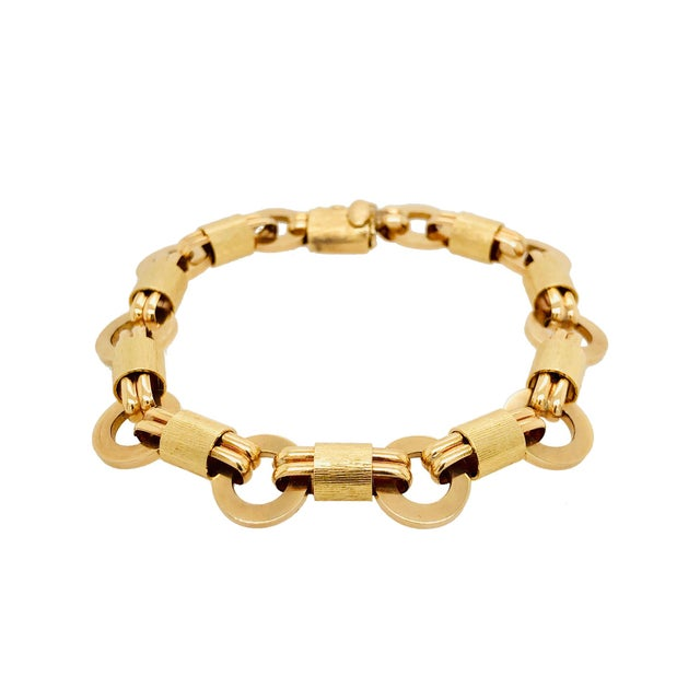 A fun vintage 14K gold link bracelet with alternating links. There are round polished disks with a textured link wrapped...