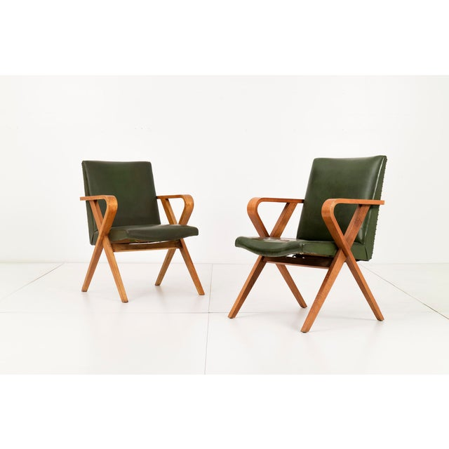 Pair of Henry Glass armchairs. Green leather seat with metal rivets alining the back. Angular bentwood frame with curved...