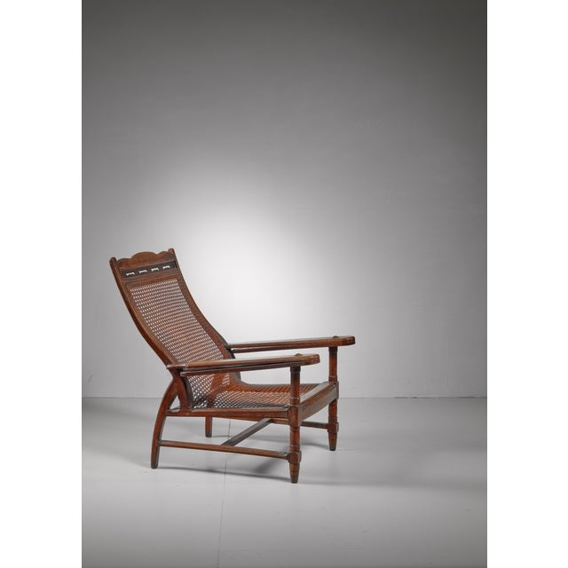 An wonderfully carved Italian planter's chair from around 1900, made of teak with brass connections and a woven cane...