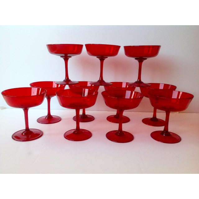 We have a gorgeous set of 11 Mid-Century ruby red coupe champagne glasses for your consideration. The glasses are hand...