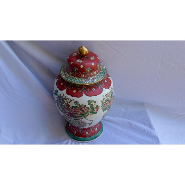 The colors of this ginger jar with lid are outstanding in fuchsia, green, white and sand. The piece has a Chinese hallmark...