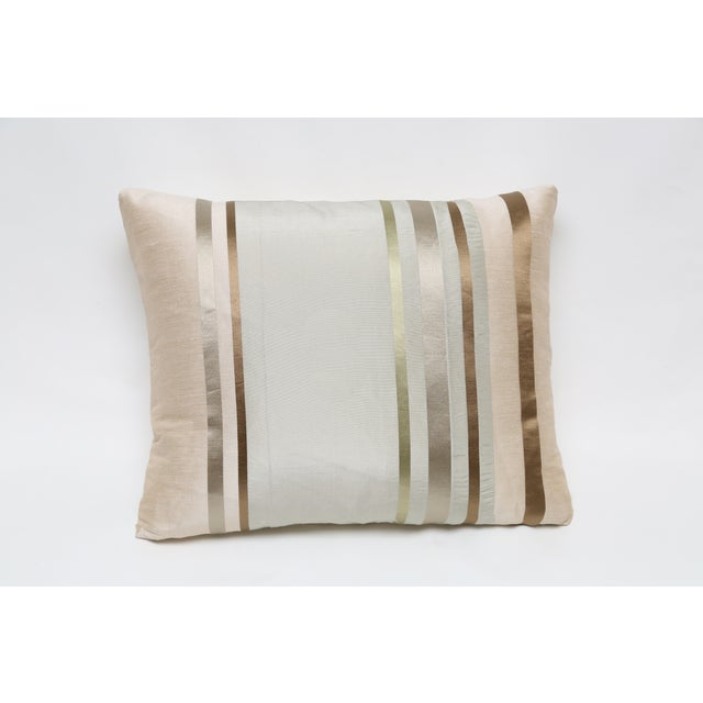 A pillow that is silk and viscose with a gold bronze stripe front and knife edge seam. It has a color matched zipper.