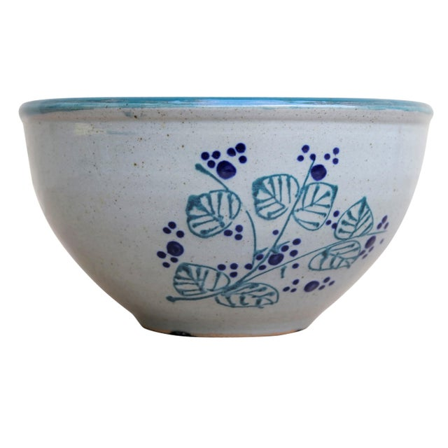 A set of two matching earthenware bowls. The inside is glazed with a rich sea blue. On the exterior is a simple plant...