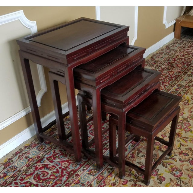 Description: This is a set of 4 late 20th Century Asian teak Chinese style stacking nesting tables, c1980-1990s. Each...