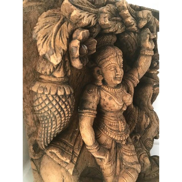 Intricately carved wooden icon of Vishnu goddess.