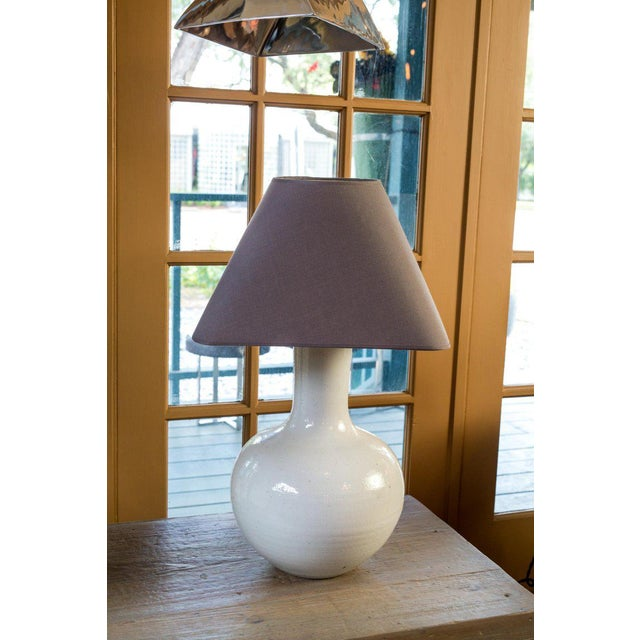 Two white glazed table lamps with bulbous bodies and slender necks. Sold with complimentary dark gray linen shades. Listed...