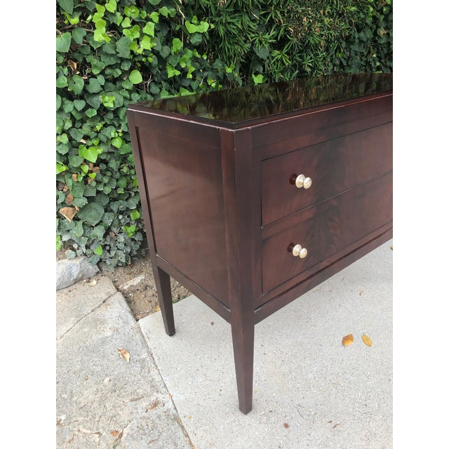A richly grained mahogany chest by Thomas O'Brien for Hickory Chair Company. The tailored beauty has a pair of roomy...