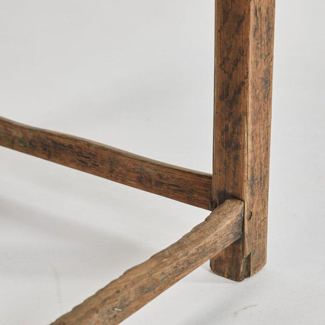 A rustic stool with black upholstered top, originating in France, circa 1940.