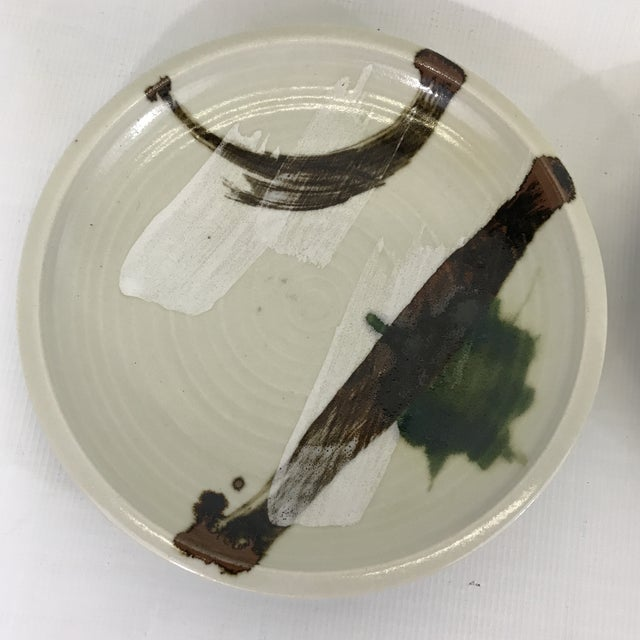 Pair of vintage art pottery plates with brown and green abstract brush stroke decoration.