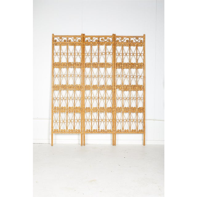 Vintage 1970's three panel folding screen or room divider made of rattan in the manner of Hollywood Regency.