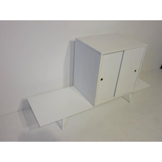 A two-piece Paul McCobb sliding door cabinet on bench with brass pull hole surrounds, conical legs and retaining the...