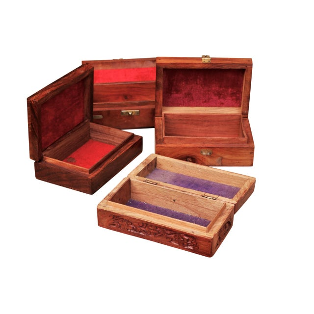 A set of four intricately carved trinket boxes with brass inlay. All have a decorative gold vine motif. Rich detailed...