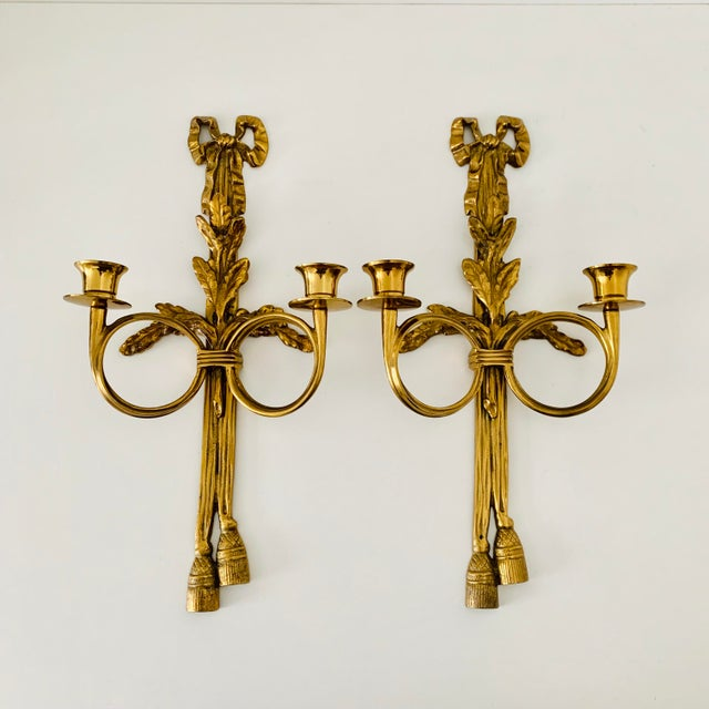 A pair of French neoclassical wall appliqués or scones, each styled with 2 arms French horns, ribbon top, and tassels...