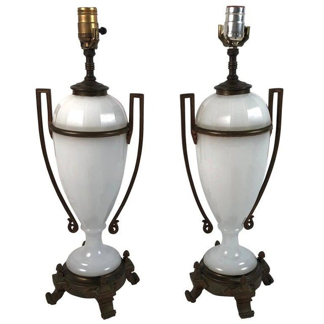 A pair of Louis XVI style neoclassical white opaline glass and ormolu lamps, each vase with rectangular strap ormolu...