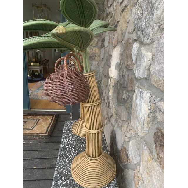 Pair of Mario Lopez palm tree table lamps made of pencil reed and wicker. These lamps consist of 6 palm leafs and 3...