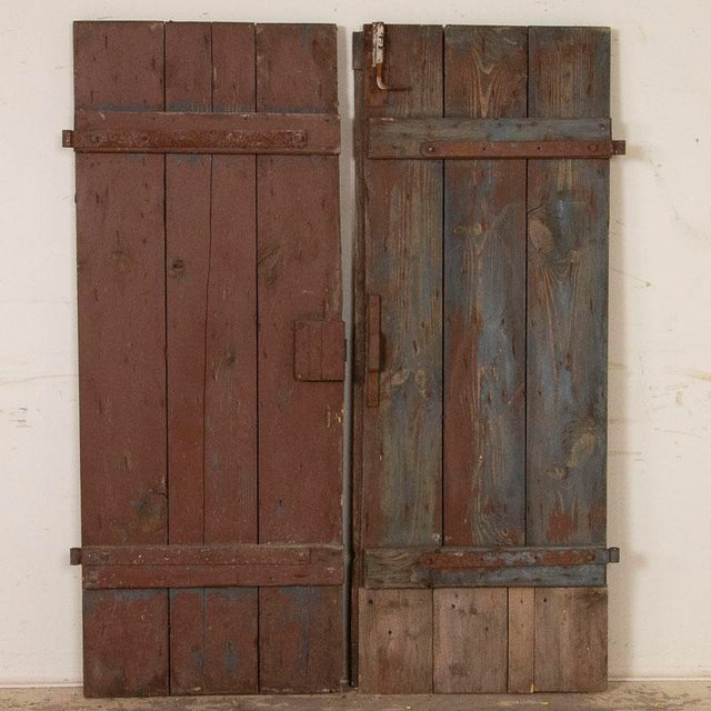 This pair of original brown painted doors have the weathered, aged appeal that create a unique focal point as interior...