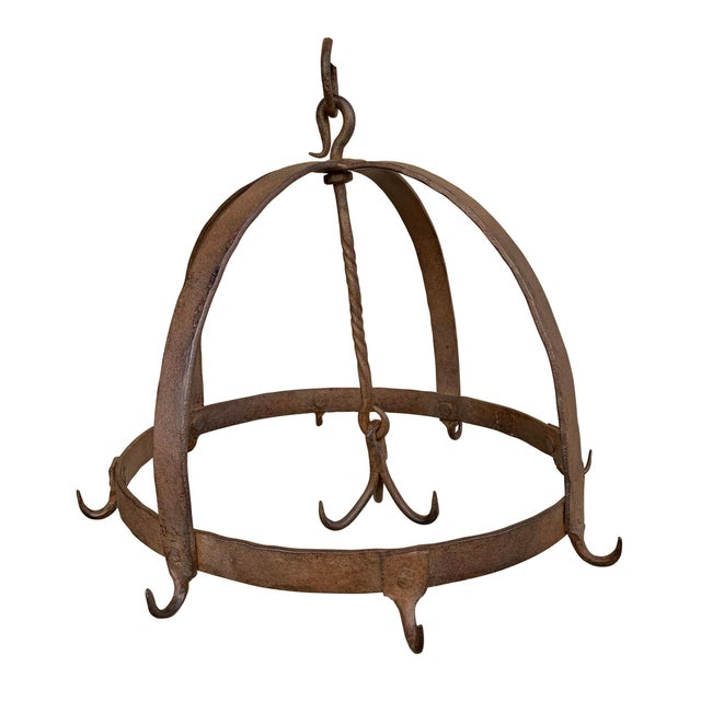 A beautiful 18th century French handwrought iron game rack with one outer ring with eight hooks, and three more hooks that...
