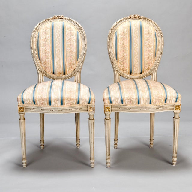 Set of eight 1920's French Louis XVI style dining chairs with carved and painted wood frames. Rounded cameo backs have a...