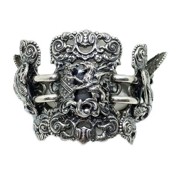 Circa 1940s to 1950s Napier silver tone metal ornate link bracelet embellished with raised griffon and shield motifs. The...