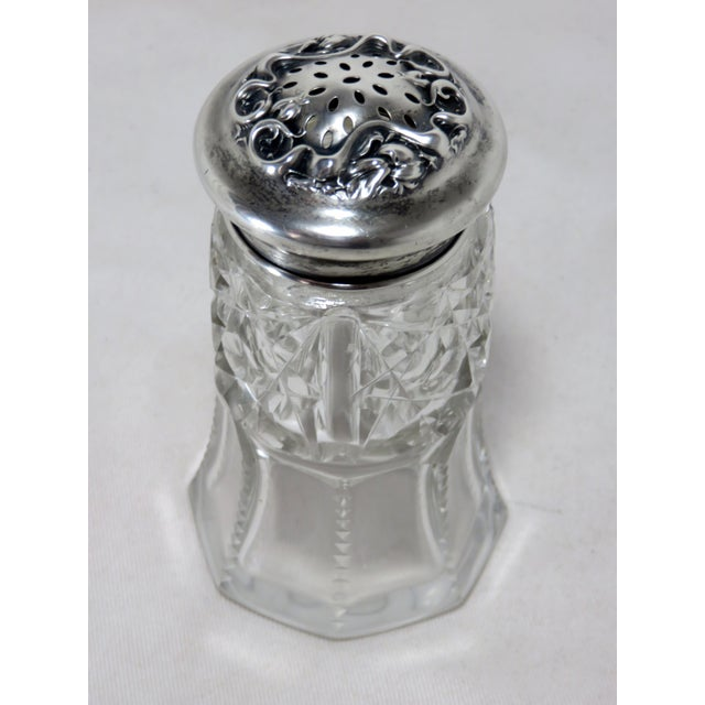 This is an antique sugar shaker from the early 20th century. The piece is made of crystal and sterling silver, done in a...