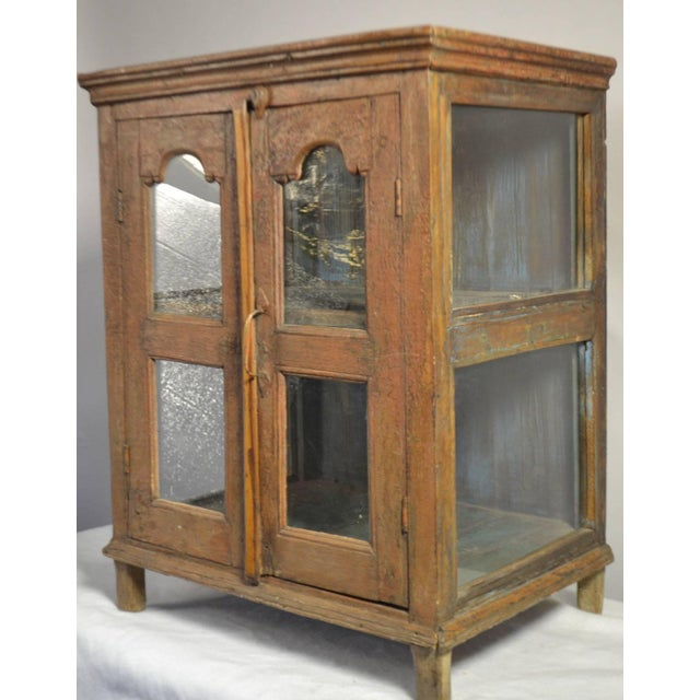 Small painted wood hanging shelf with glass doors, circa 1790.