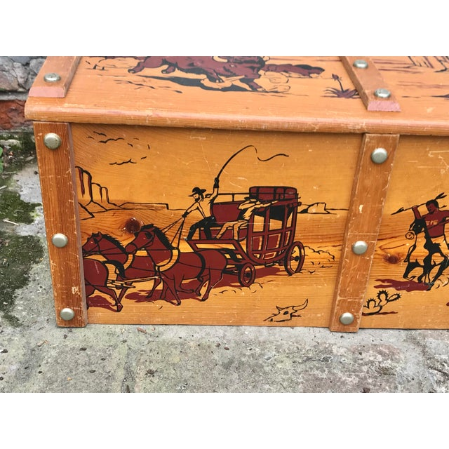 Fabulous vintage 1950's cowboys and Indians toy chest. Made of wood with rope handles. The images are painted on in browns...