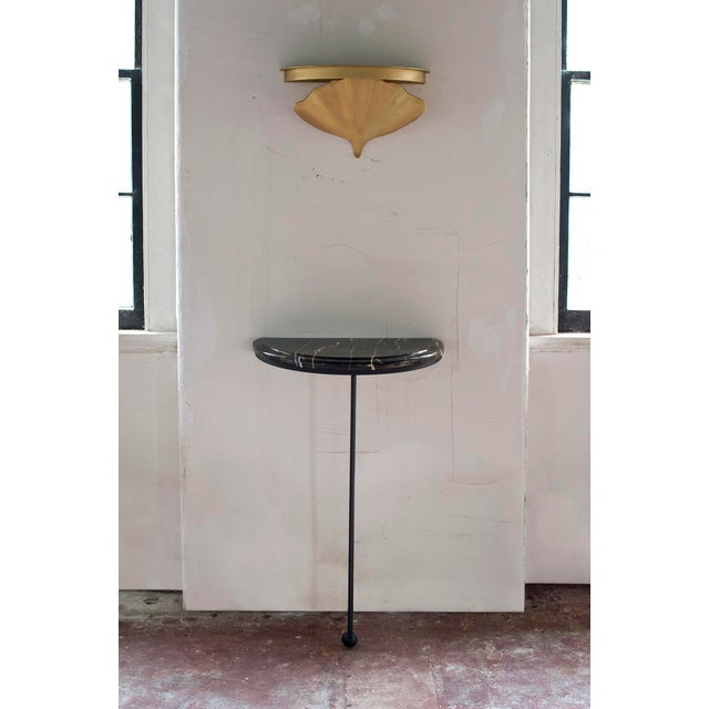 Wall mounted steel base with stone demilune top.