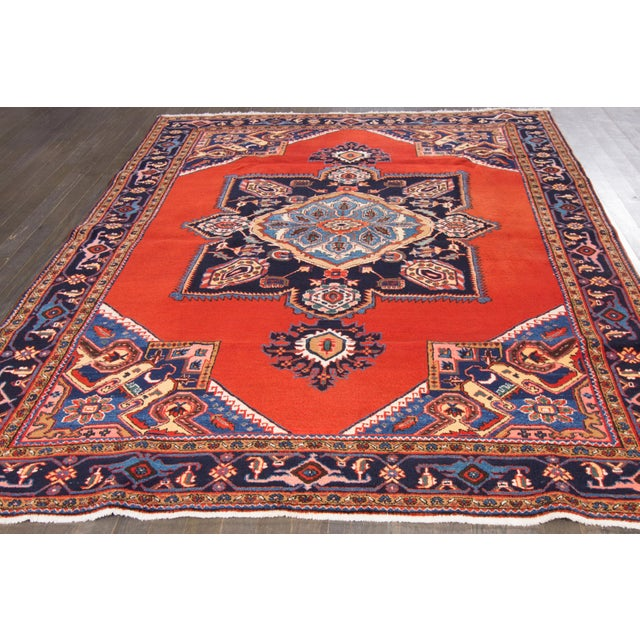 Vintage, hand-knotted Persian rug with a medallion design on a red field. This rug has a fiery, vibrant color and is ready...