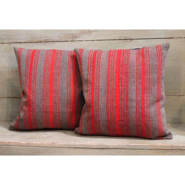 This Classic pair of striped wool pillows is constructed from late 19th century fabric and feature varying sizes of red...