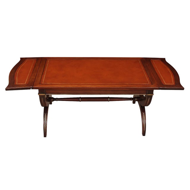 Regency style drop-leaf coffee table From the 1960's. This solid wood table features an inset leather top with gold...