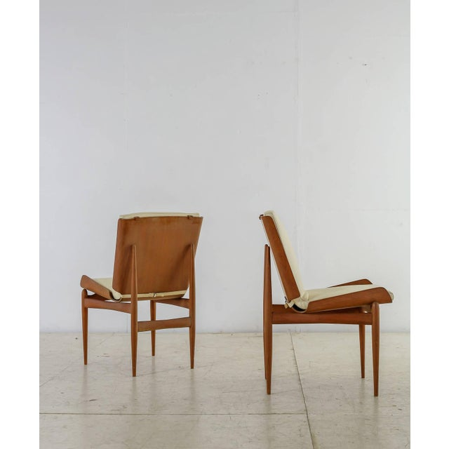 A beautiful pair of side chairs. The seat is made of folded plywood with a white leather seat pad that is attached to the...