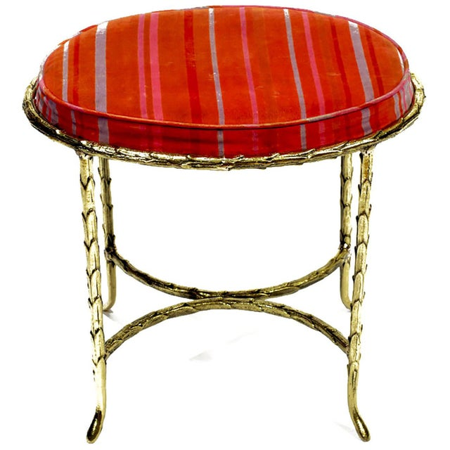 Vanity stool, or bench, cast in solid bronze with a palm-form surface. Seat is upholstered in a vivid fuschia and lavender...