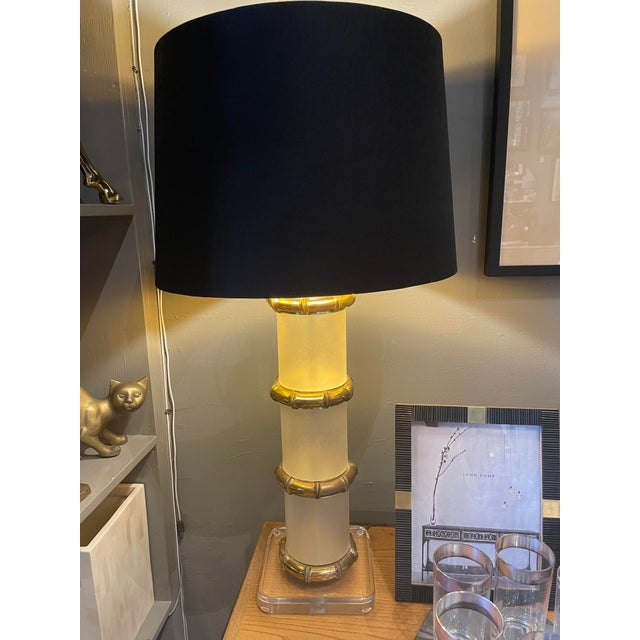 Stunning lamps from the 1970s with brass bamboo styled detailing and lucite. With a black linen shade this pair of lamps...