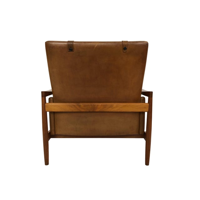 This is a sleek and unusual Danish modern wood and brown leather accent chair by Erik Worts. The piece was made circa 1960.