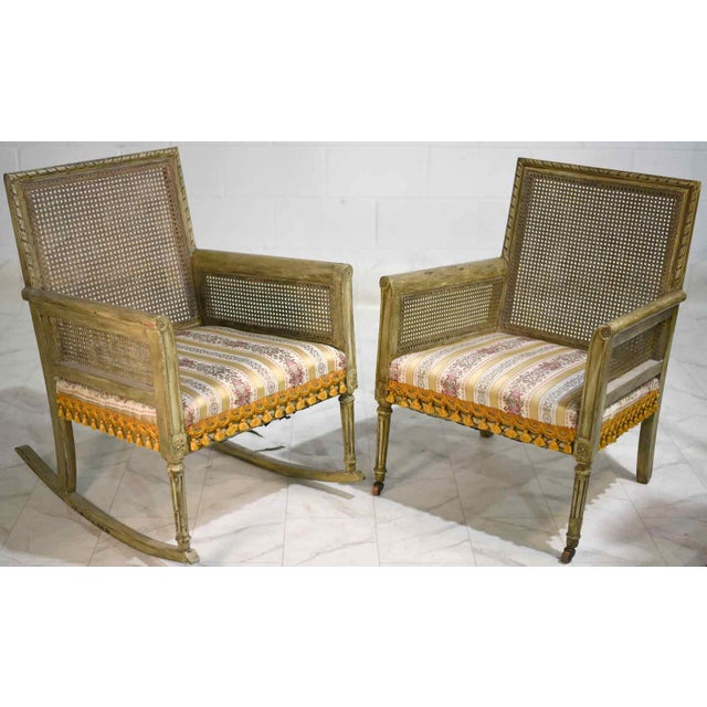 Remarkable pair of distressed finish green-grey painted armchair and rocking chair. These cane-backed chairs have a rustic...