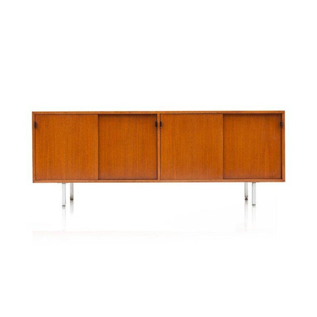 Modern credenza in teak. The credenza has four sliding doors, each provided with elegant and beautifully patinated black...